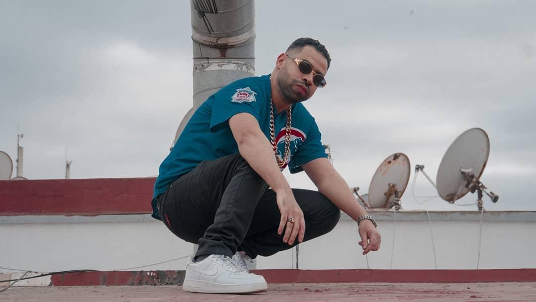 Le rappeur marocain Noyzzz posant sur le toit d'une bâtisse.
